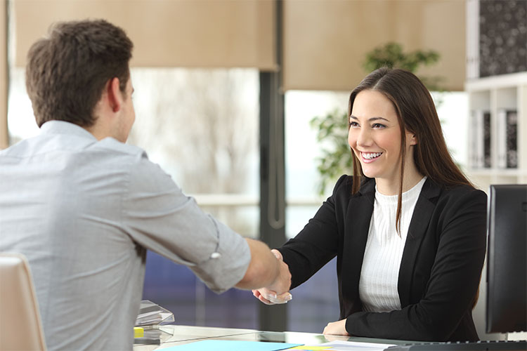 Woman and man shaking hands in office setting